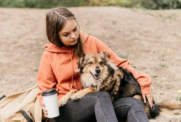 Bela jovem acariciando seu cachorro Foto gratuita