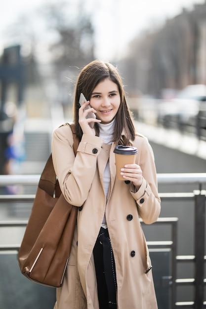 Bela jovem andando pela rua, segurando o telefone e a xícara de café Foto gratuita
