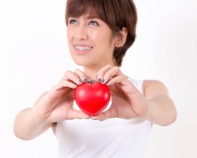 Bela jovem ásia mulher com coração vermelho Foto Premium