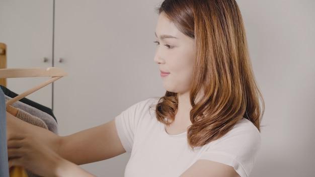 Bela jovem asiática atraente escolhendo sua roupa de roupa de moda no armário em casa Foto gratuita