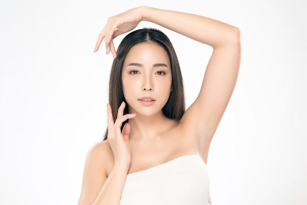 Bela jovem asiática tocando a bochecha macia e sorria com a pele limpa e fresca. felicidade e alegria com, isolado no branco, beleza e cosméticos, Foto Premium