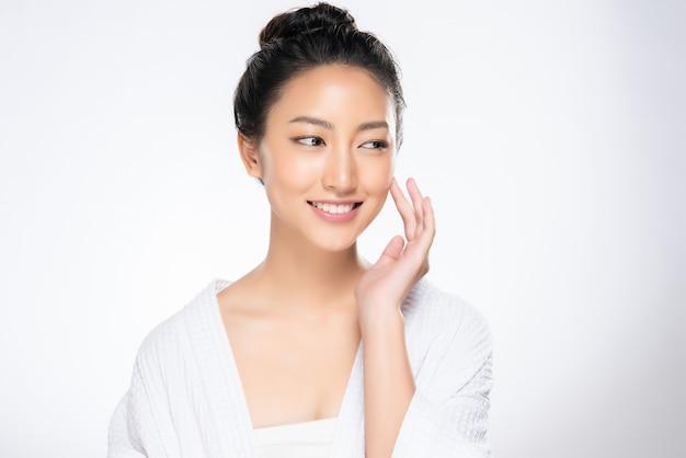Bela jovem asiática tocando a bochecha macia e sorria com a pele limpa e fresca Foto Premium