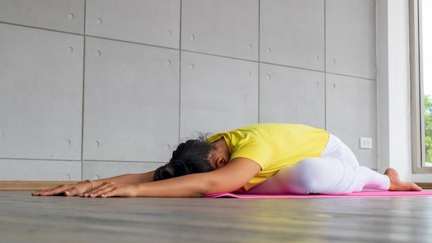Bela jovem asiática vestindo roupas esportivas praticando ioga no estúdio, luz natural. conceito: poses de ioga para iniciantes. Foto Premium