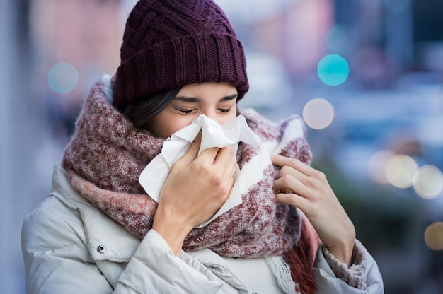 Bela jovem assoando o nariz com um lenço de papel ao ar livre no inverno Foto Premium