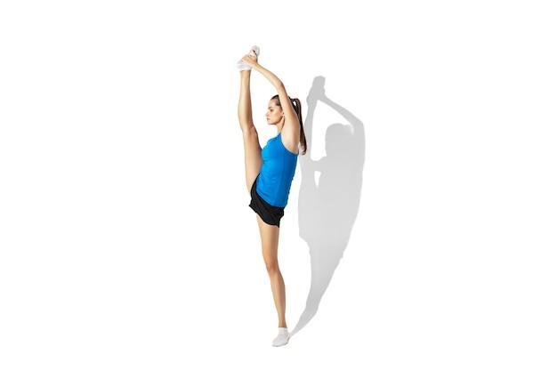 Bela jovem atleta feminina, alongamento, treinamento no espaço em branco, retrato com sombras Foto gratuita