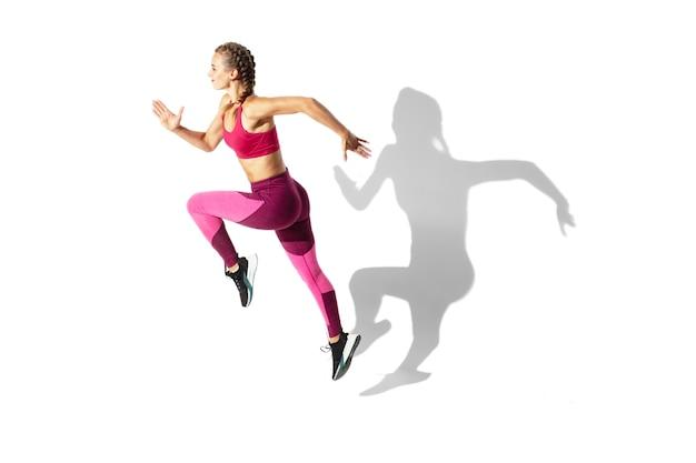 Bela jovem atleta praticando no espaço em branco, retrato com sombras Foto gratuita