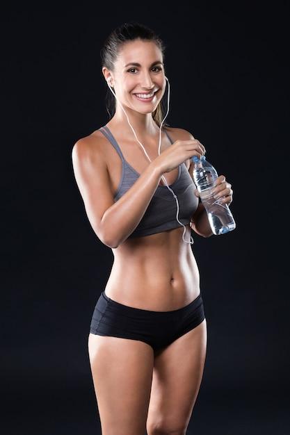 Bela jovem bebendo água depois de fazer exercícios sobre fundo preto. Foto gratuita