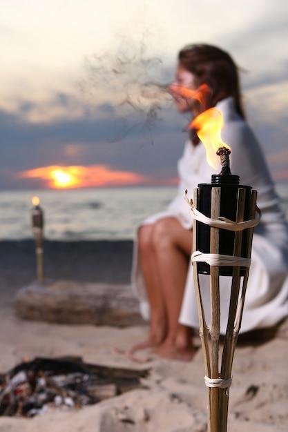 Bela jovem bebendo vinho na praia Foto gratuita