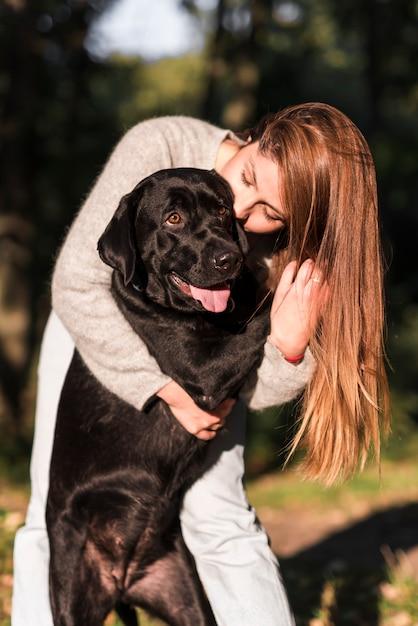 Bela jovem beijando seu labrador preto no parque Foto gratuita