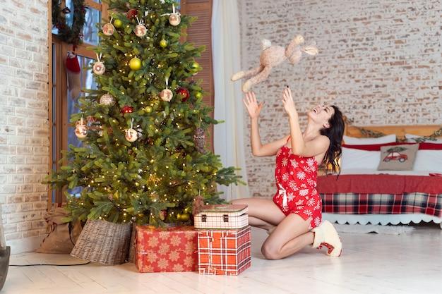 Bela jovem brincando com um ursinho de pelúcia na árvore de natal Foto gratuita