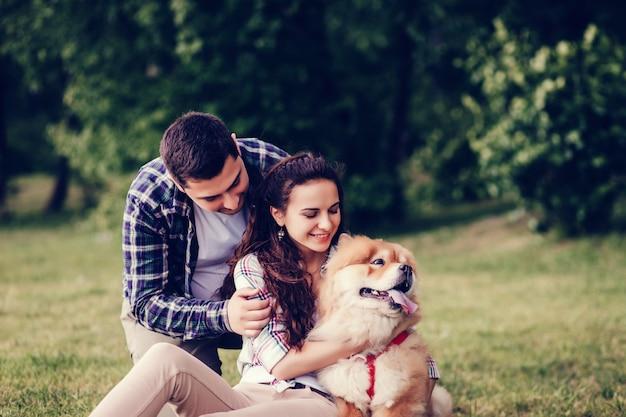 Bela jovem casal e cachorro Foto Premium