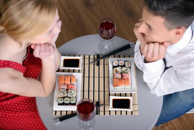 Bela jovem casal sentados juntos e comendo. Foto Premium