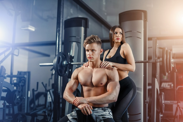 Bela jovem casal sexy desportivo mostrando muscular e treino no ginásio durante photoshooting Foto Premium
