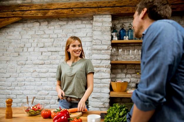 Bela jovem casal sorrindo enquanto cozinhando na cozinha em casa Foto Premium
