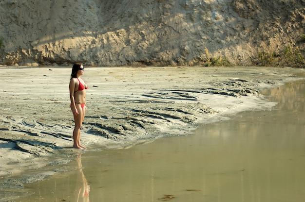 Bela jovem caucasiana magra de biquíni e óculos escuros em pé na costa arenosa e suja perto do lago Foto Premium