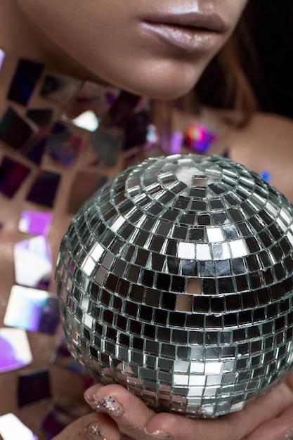 Bela jovem caucasiana segurando bola de discoteca Foto Premium