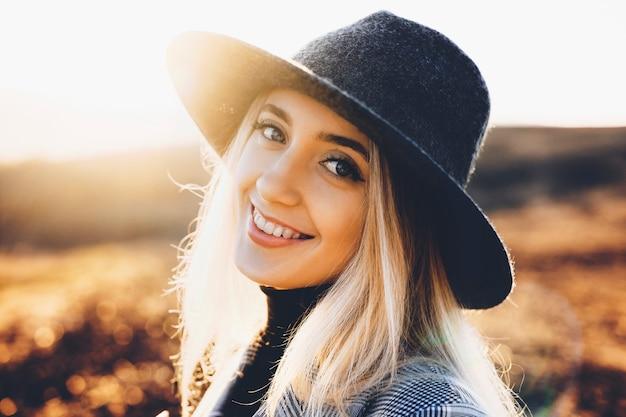 Bela jovem com chapéu estiloso, sorrindo alegremente e olhando para a câmera em pé no fundo desfocado da natureza outono em dia ensolarado. Foto Premium
