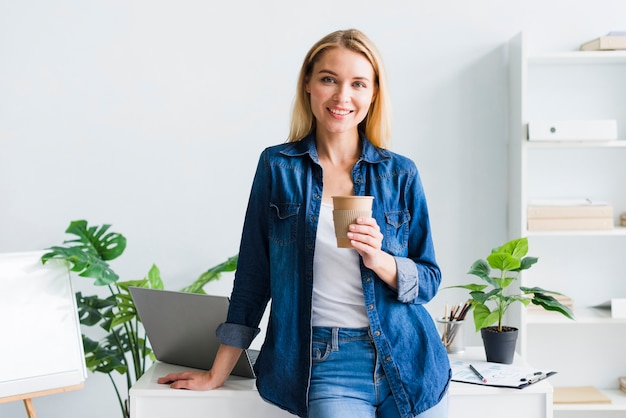 Bela jovem com copo de papel no local de trabalho Foto gratuita