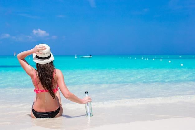 Bela jovem com garrafa sentado na praia Foto Premium