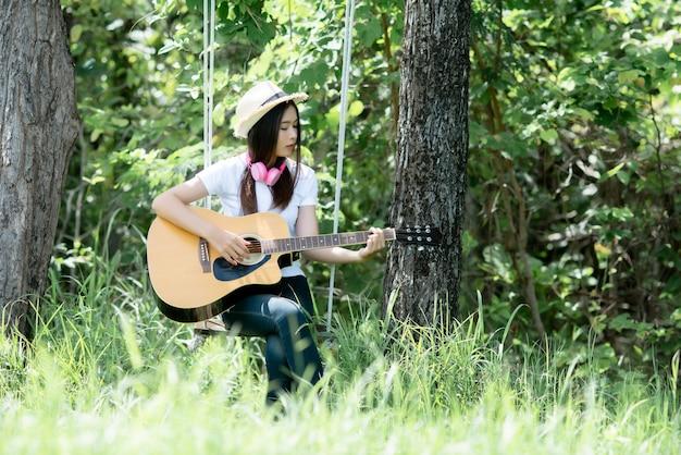Bela jovem com guitarra acústica na natureza Foto gratuita