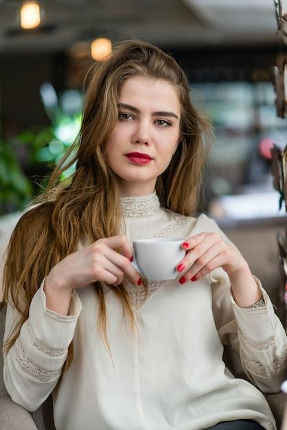 Bela jovem com maquiagem profissional e penteado sentado no restaurante. Foto Premium