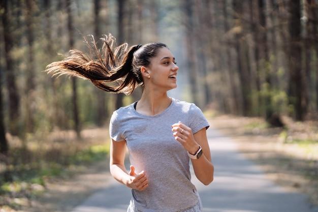 Bela jovem correndo no parque verde em dia de verão ensolarado Foto gratuita