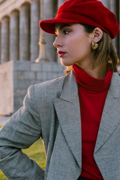 Bela jovem de boné vermelho com brinco de ouro nas orelhas dela, olhando para longe Foto gratuita