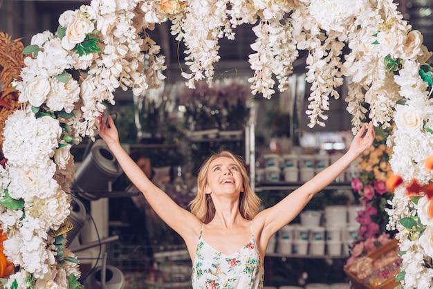 Bela jovem de pé debaixo da entrada curva decorada, levantando os braços e olhando para cima Foto gratuita