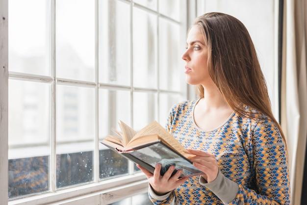 Bela jovem de pé perto da janela, segurando o livro na mão, olhando para longe Foto gratuita