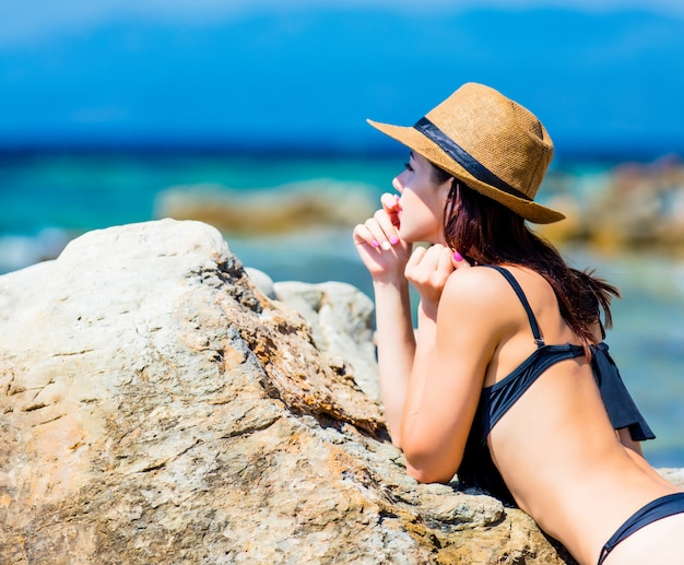Bela jovem de pé perto de pedra grande na praia e olhando para o mar na grécia Foto Premium