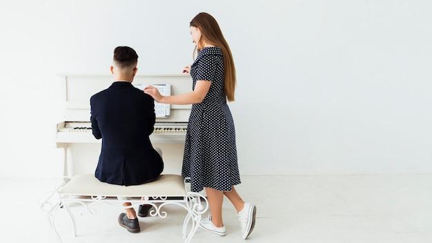 Bela jovem de pé perto do homem tocando piano Foto gratuita