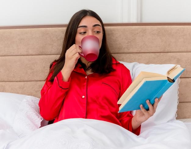 Bela jovem de pijama vermelho relaxando na cama Foto gratuita