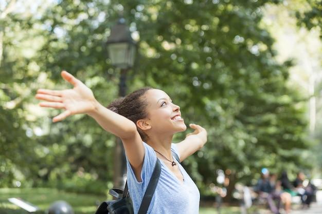 Bela jovem de raça mista no parque, sensação de liberdade Foto Premium