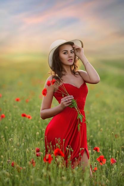 Bela jovem de vestido vermelho e chapéu branco anda por aí campo com papoulas Foto gratuita