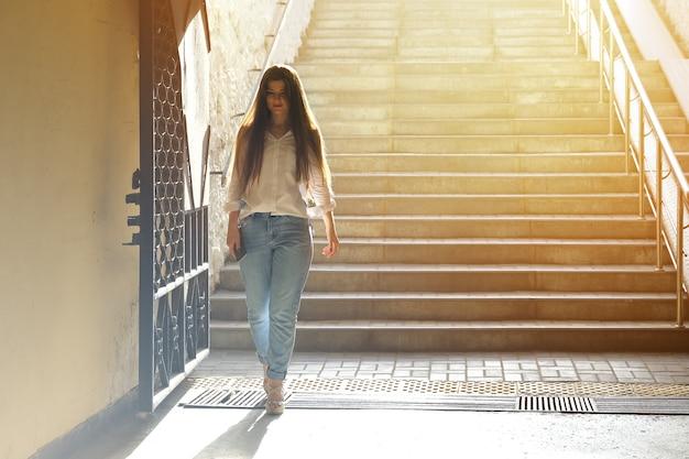 Bela jovem desceu os degraus da passagem subterrânea Foto Premium