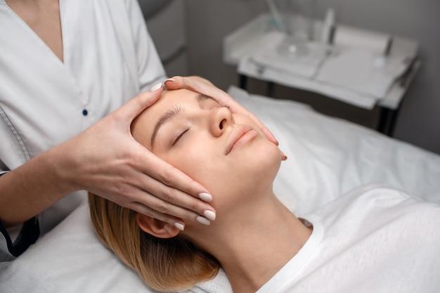 Bela jovem desfrutar de massagem de rosto no sofá. beautisian tocá-lo com as mãos. ela está na sua cabeça. Foto Premium