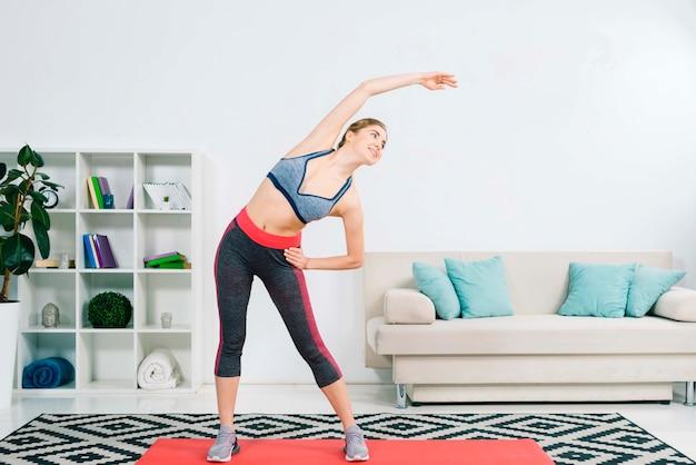 Bela jovem desportiva, exercitando-se na moderna sala de estar Foto gratuita