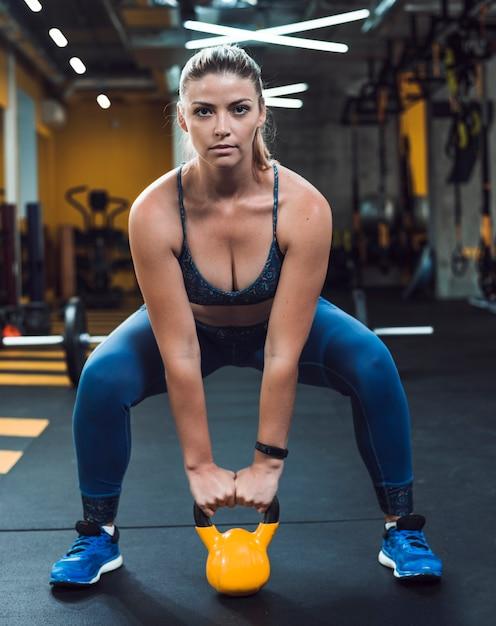 Bela jovem ding treino com bola de chaleira no clube de fitness Foto Premium