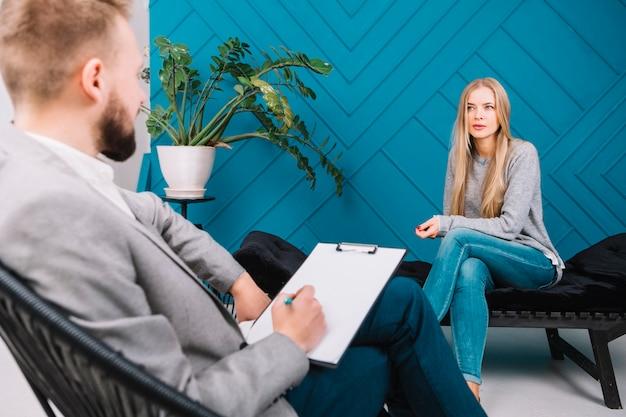 Bela jovem discutindo seus problemas com psicólogo masculino sentado na cadeira Foto gratuita