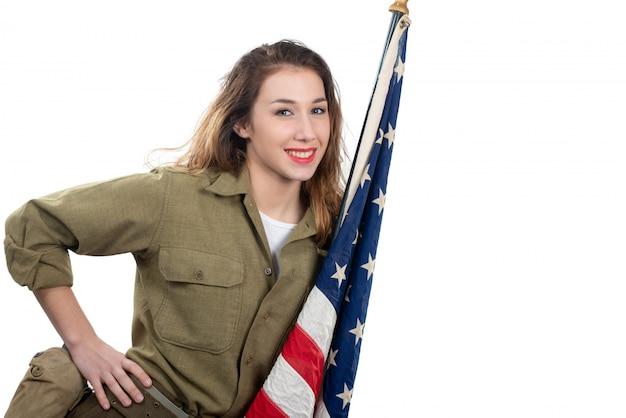 Bela jovem em wwii uniforme nos com a bandeira americana Foto Premium