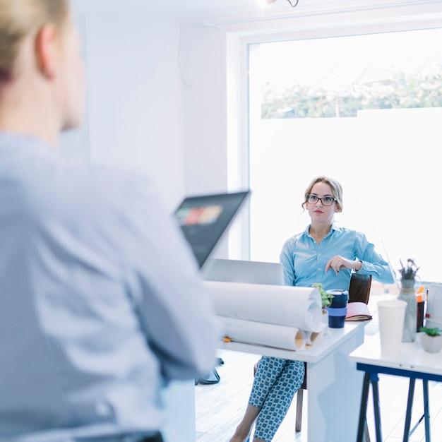 Bela jovem empresária sentado na cadeira, ouvindo seu colega em reunião Foto gratuita