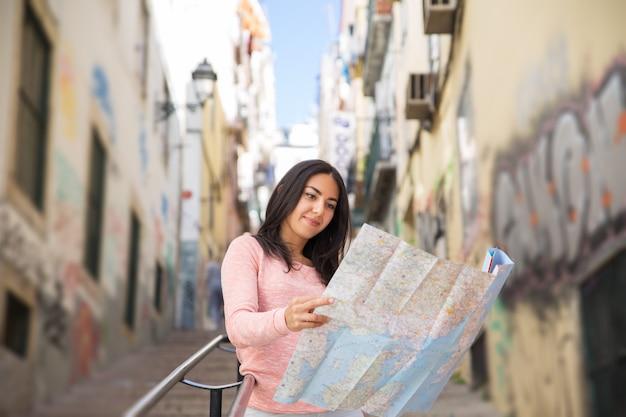 Bela jovem estudando o mapa de papel nas escadas da cidade Foto gratuita