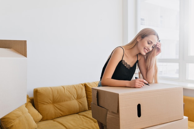 Bela jovem etiquetando caixa de papelão, segurando o marcador na mão, indo para empacotar coisas, mudando-se para um novo apartamento, apartamento, casa. garota feliz na sala com sofá amarelo, ela vestindo blusa preta. Foto gratuita