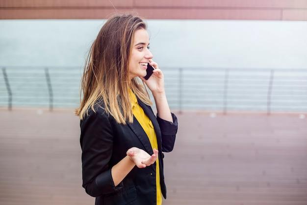 Bela jovem falando no celular ao ar livre Foto Premium