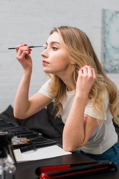 Bela jovem fazendo ela mesma maquiagem sentado no estúdio Foto gratuita