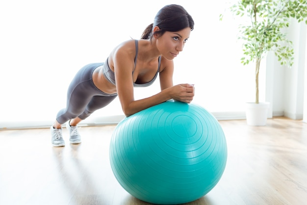Bela jovem fazendo exercício de pilates com bola de fitness em casa. Foto gratuita