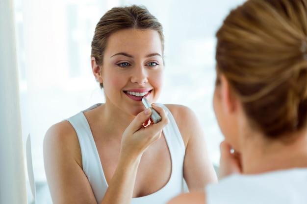 Bela jovem fazendo maquiagem perto do espelho em casa. Foto Premium