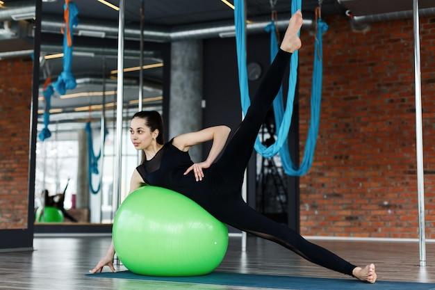 Bela jovem flexionando muscels abdominais na bola verde no ginásio Foto gratuita