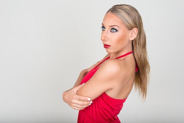 Bela jovem loira contra uma parede branca Foto Premium