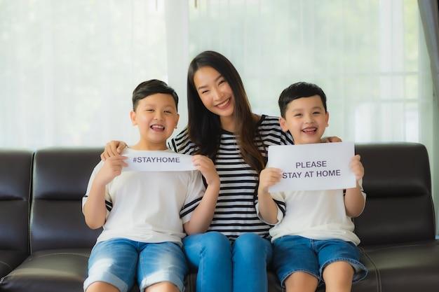 Bela jovem mãe asiática com seus dois filhos mostra papel para ficar em casa para proteger o coronavírus Foto gratuita